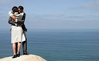 View of a couple hugging each other on a cliff