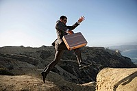 Business man jumping over a cliff holding briefcase