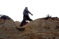 Business man walking on edge of cliff