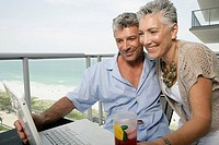Mature couple on a terrace using a laptop