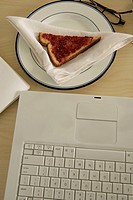 Laptop and slice of bread on plate, close-up