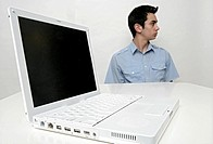 View of a teenage boy and a laptop on a table (thumbnail)