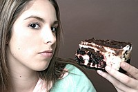 Portrait of a teenage girl holding a piece of cake (thumbnail)
