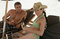 View of a couple relaxing on deck chairs