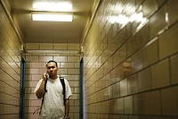 Teenage boy 15-17 standing in passageway, on the phone (thumbnail)