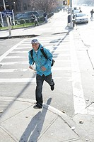 Young man crossing road