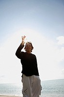 Man raising hand at the beach, looking at camera