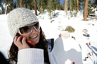 Woman talking on cell phone on a ski slope