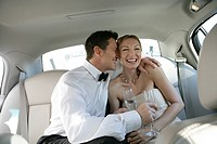 Mature couple laughing in the backseat of a car