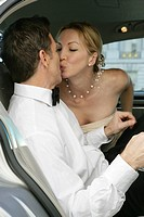 Mature couple kissing in the backseat of a car