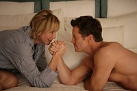 Mature couple arm wrestling in bed