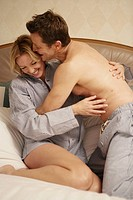 Mature couple wrestling in bed