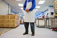 Man, wearing an apron, standing in the middle of a dessert factory
