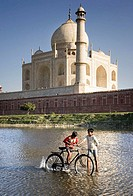 Boys playing with bike in front of the Taj Mahal, Agra. Uttar Pradesh, India