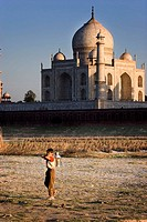 Boy with milk pot and Taj Mahal in background, Agra. Uttar Pradesh, India