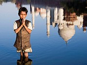 Boy praying in Yamuna River and Taj Mahal reflection, Agra. Uttar Pradesh, India