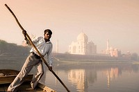 Boatman on Yamuna River with Taj Mahal in background, Agra. Uttar Pradesh, India