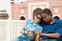 Close-up of a young couple looking at a digital camera, Taj Mahal, Agra, Uttar Pradesh, India