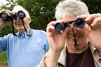 Two people, middle aged birdwatchers at Cors Caron nature reserve Tregaron,  Ceredigion mid wales, looking through binoculars at the wild birds nestin...