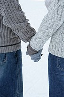 Couple holding hands wearing gloves, sweaters and jeans