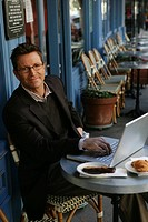 Mature man typing on a laptop at a cafe