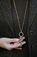 Close-up of a woman wearing a necklace with keys on it