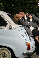 Mature couple kissing on a car