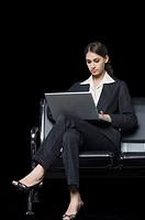 Businesswoman sitting on a bench and using a laptop