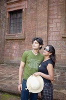 Young couple standing together in front of a wall, Goa, India