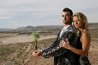 Couple in the desert, man holding a sapling (thumbnail)