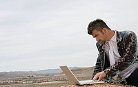 Man looking at a laptop in the desert
