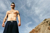 Caucasian man standing outdoors shirtless, looking at camera