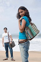 Portrait of a young woman carrying a hand bag with a young man standing in the background on the beach