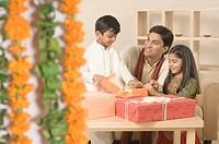 Young man sitting with his children and opening diwali gifts