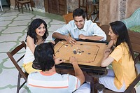 Four people playing carom
