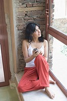 Young woman sitting on the ledge of a window and holding a mobile phone