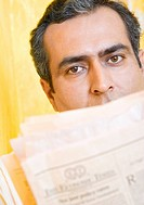 Close-up of a mid adult man with a newspaper