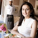 Portrait of a mid adult woman sitting in a restaurant with a chef standing in the background
