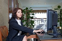 Side profile of a female receptionist working on a desktop PC in a hotel reception