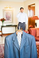 Close-up of a business suit hanging on a hanger with a businessman standing in the background