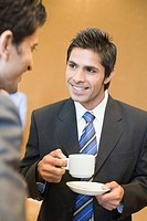 Close-up of a businessman holding a cup of tea and talking with his colleague