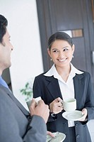 Close-up of a businessman and a businesswoman holding cups of tea