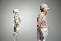 Elderly man standing near a skeleton