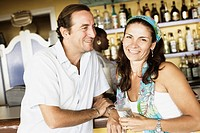 Mid adult couple at a bar counter and smiling