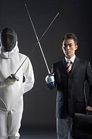 one man in business suit and a man in fencing costume practicing fencing