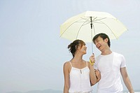 Young lovers under umbrella and smiling on beach