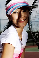 Close-up of a young woman holding tennis racket