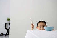 Boy holding chopsticks by table