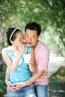 Young woman feeding ice cream to a man