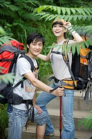 Young couple hiking together in a forest, smiling
